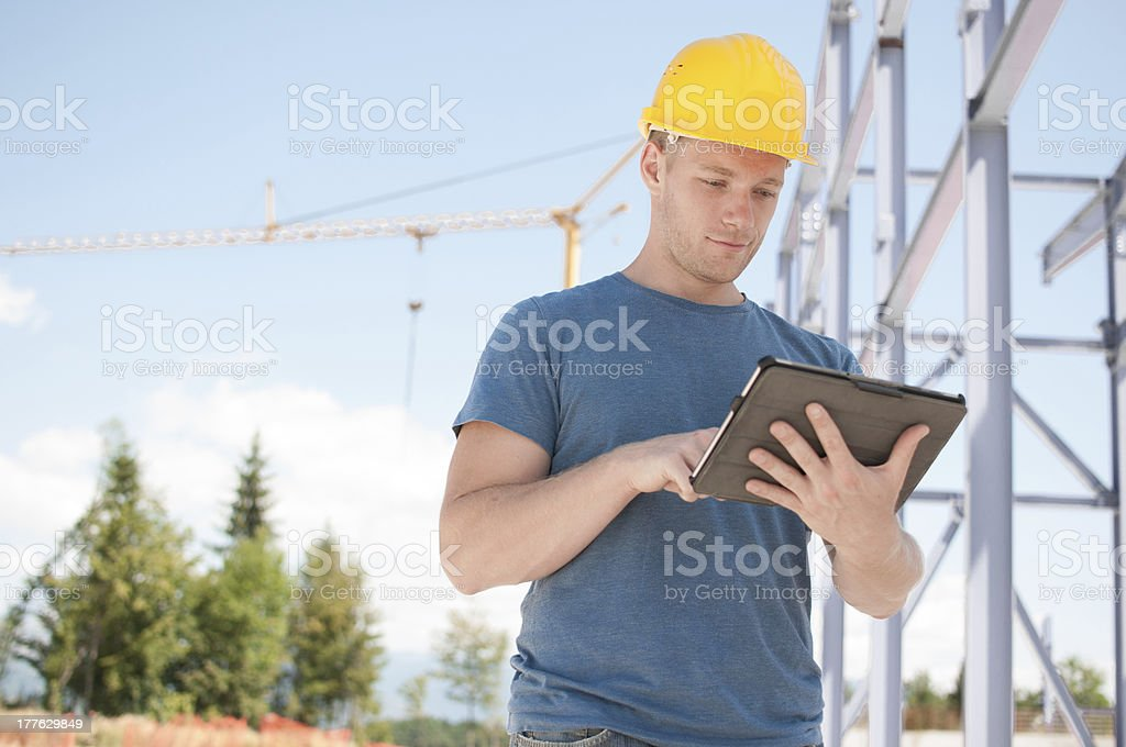 Engineer reviewing plans on digital tablet royalty-free stock photo