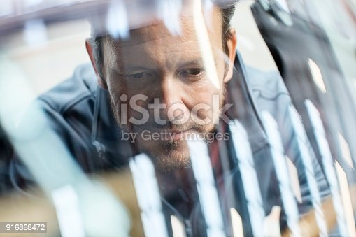Close-up of male engineer seen through car windshield. Confident male is repairing vintage vehicle in automobile industry. Technologist is smiling while working in showroom.