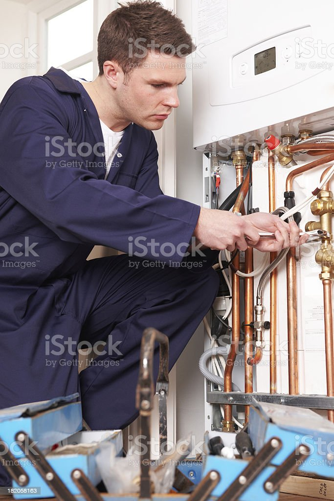 Engineer Servicing Central Heating Boiler royalty-free stock photo