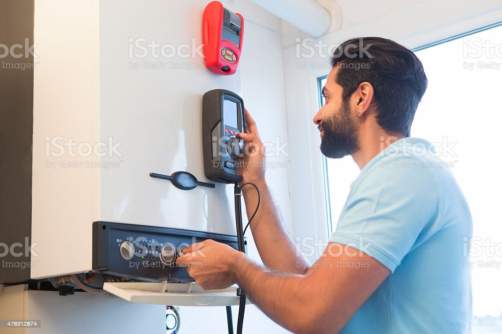 Engineer Servicing Central Heating Boiler Stock Photo - Download Image Now