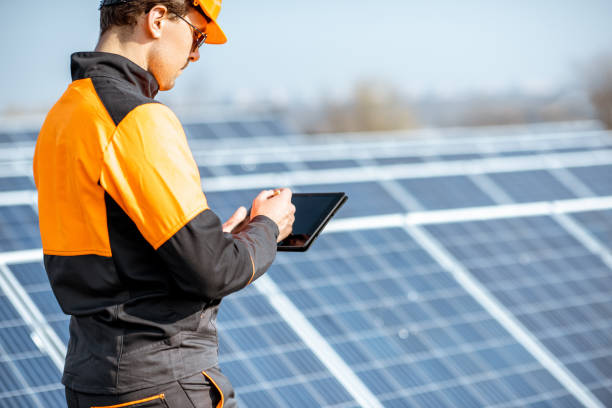 Engineer servicing solar panel on electric plant Engineer in protective workwear carrying out service of solar panels with digital tablet on a photovoltaic rooftop plant. Concept of maintenance and setup of solar power station power occupation stock pictures, royalty-free photos & images