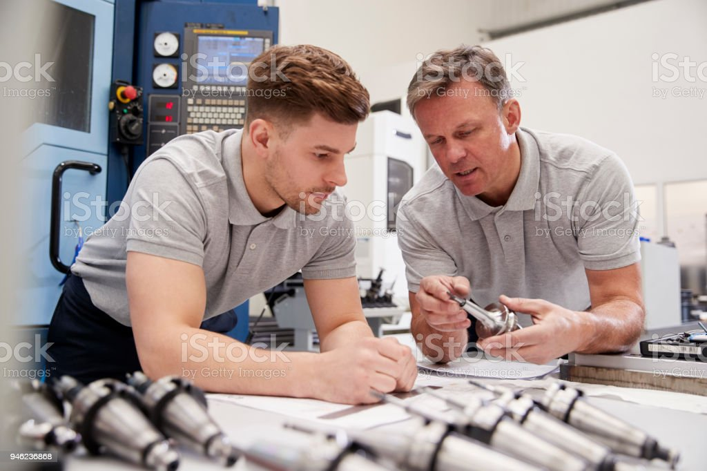 Engineer Showing Apprentice How To Measure CAD Drawings royalty-free stock photo