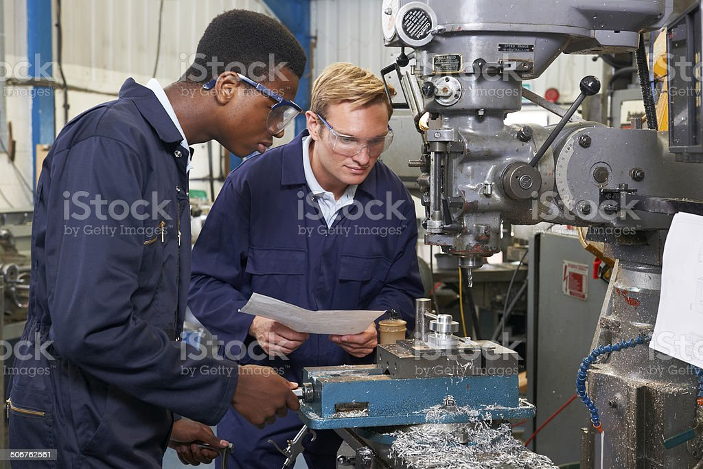 Engineer Showing Apprentice How to Use Drill In Factory stock photo