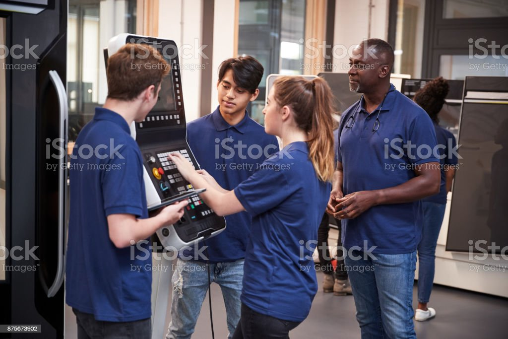 Engineer Showing Apprentices How To Use CNC Tool Making Machine stock photo