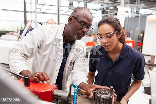 istock Engineer showing equipment to a female apprentice, close up 862721458