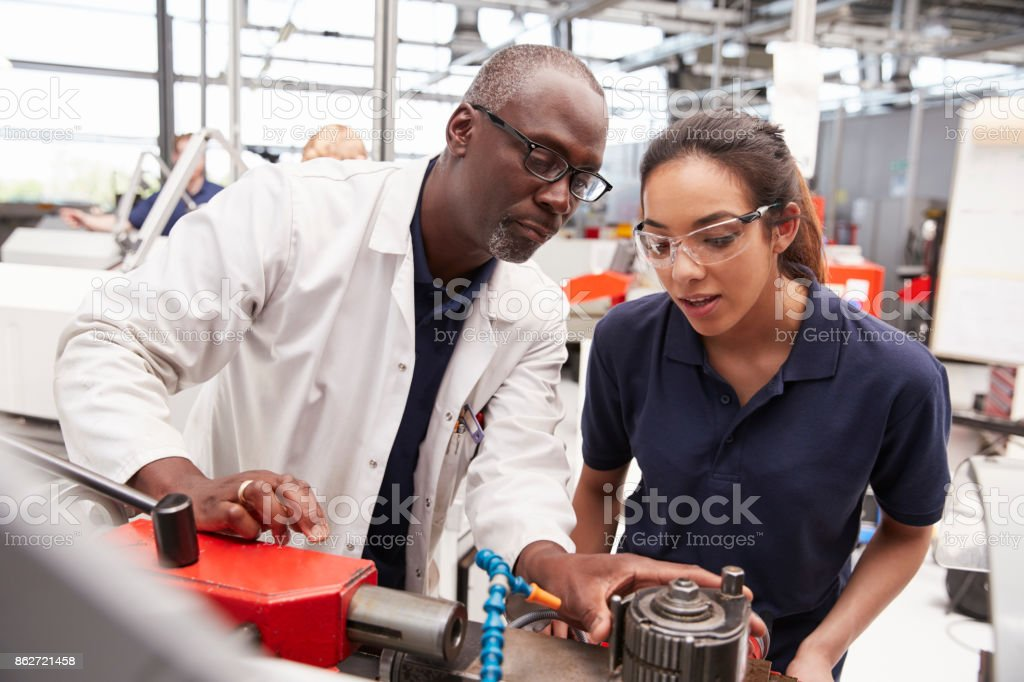 Engineer showing equipment to a female apprentice, close up stock photo