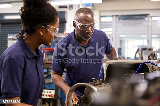 istock Engineer Showing Female Teenage Apprentice How To Use Lathe 876961820