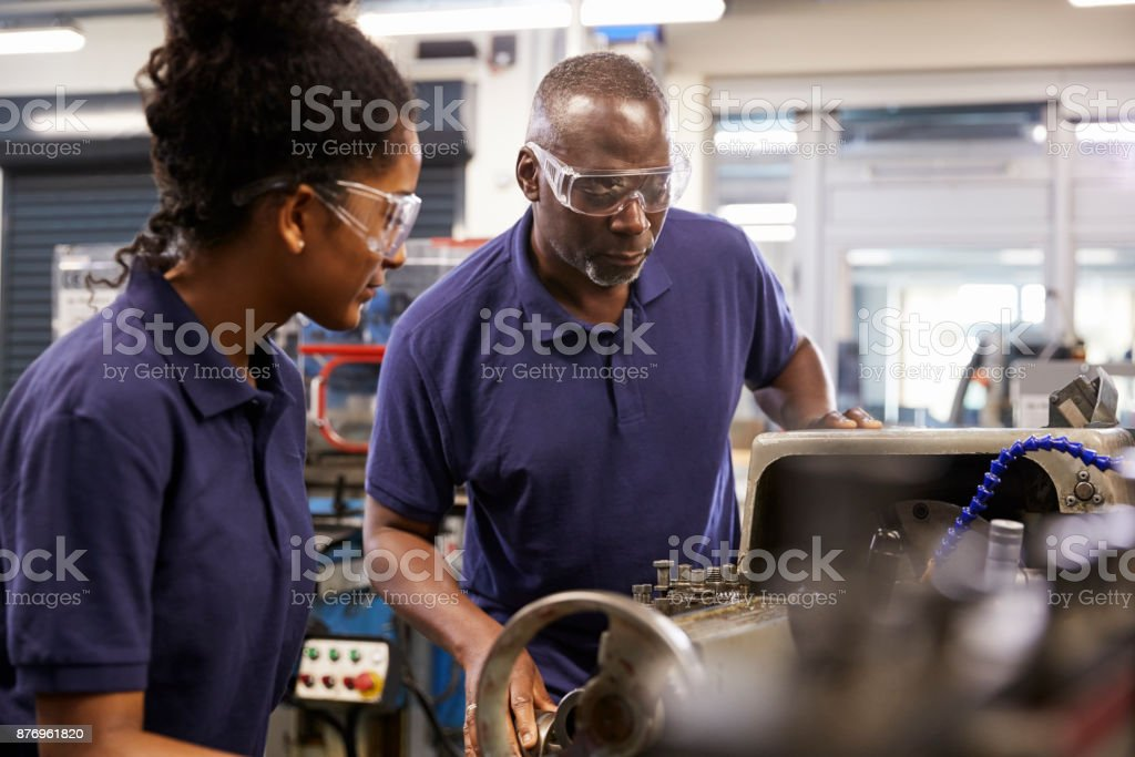 Engineer Showing Female Teenage Apprentice How To Use Lathe stock photo