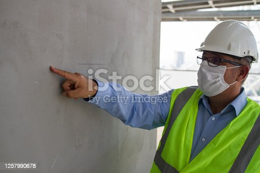 Engineer Showing Incorrect Point On The Plastered Wall