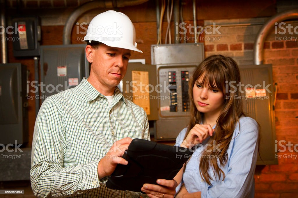 Engineer showing plans to a woman by a circuit breaker stock photo