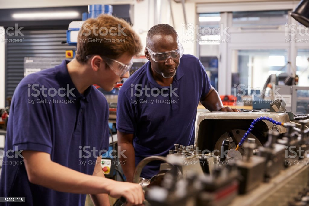 Engineer Showing Teenage Apprentice How To Use Lathe stock photo