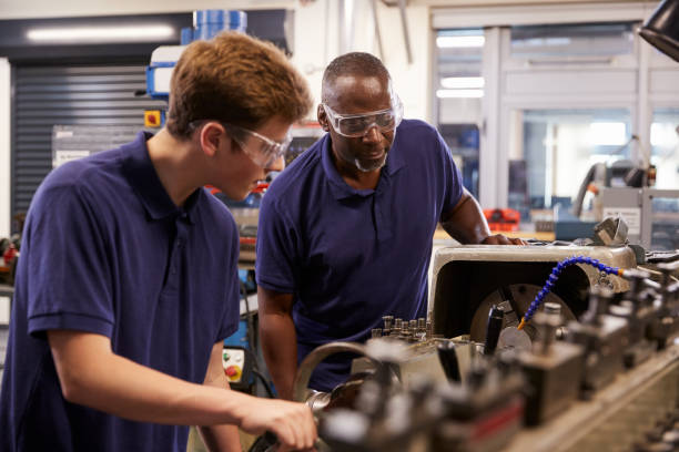 engineer showing teenage apprentice how to use lathe - vocational training stock photos and pictures