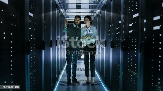 istock IT Engineer Shows Working Data Center / Server Room to Female Chief Engineer who Holds Tablet Computer. 802301280