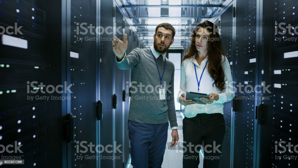 IT Engineer Shows Working Data Center / Server Room to Female Chief Engineer who Holds Tablet Computer. stock photo