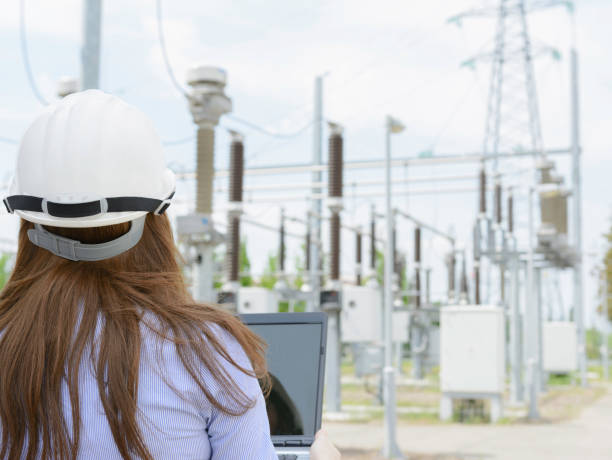 Engineer standing in electric power substation and working on laptop stock photo