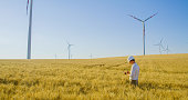 Side view shot of an engineer in a white helmet and a button down shirt standing in a wheat with wind turbines and using his mobile phone, Austria