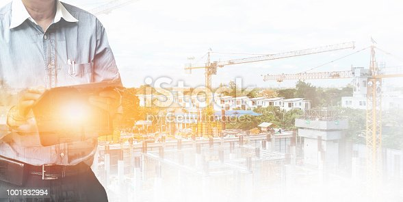 istock Engineer standing using tablet control and manage work at construction site. 1001932994