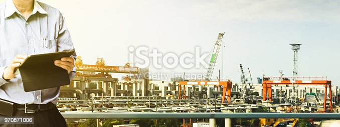 istock Engineer standing using tablet control and manage work at construction site. 970871006