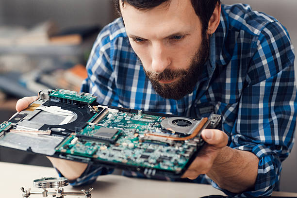 Engineer studying computer motherboard, close-up stock photo