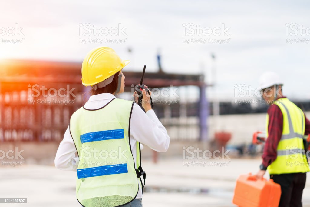 Engineer surveyor using walkie-talkie at construction site