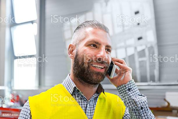 Engineer Talking On Smart Phone At Work Stock Photo - Download Image Now