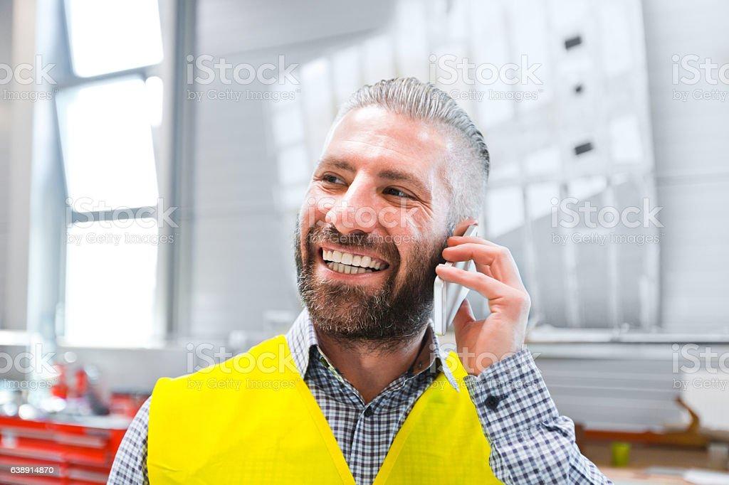 Engineer talking on smart phone at work Happy engineer talking on smart phone at work. Adult Stock Photo