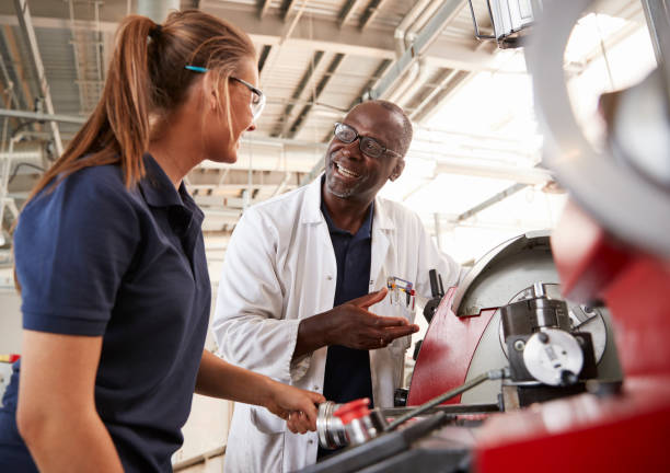 Engineer talking to female apprentice by machinery, close up stock photo