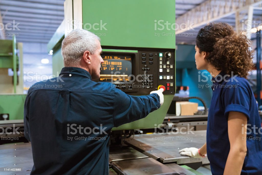 Engineer teaching apprentice in factory Mature engineer explaining female trainee over puller machine. Male instructor is teaching apprentice in factory. They are working in industry. 30-34 Years Stock Photo