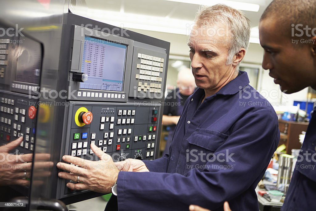 Engineer Teaching Apprentice To Use Computerized Lathe stock photo