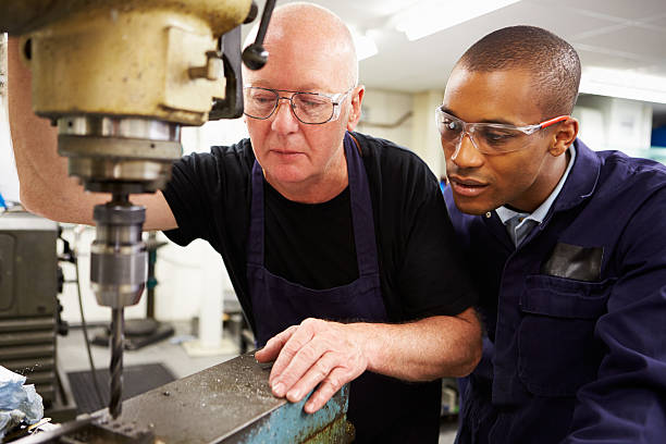 engineer teaching apprentice to use milling machine - vocational training stock photos and pictures