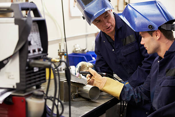 Engineer Teaching Apprentice To Use TIG Welding Machine Engineer Teaching Apprentice To Use TIG Welding Machine At Work metal worker stock pictures, royalty-free photos & images
