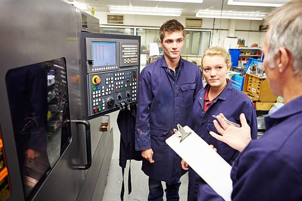 Ingenieur Unterricht Auszubildenden zu einem computergesteuerten Drehmaschine – Foto
