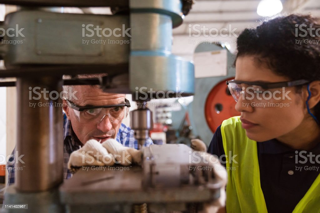 Engineer teaching female apprentice in factory Instructor teaching female apprentice to use machinery. Engineer is with trainee in factory. They are in industry. 30-34 Years Stock Photo