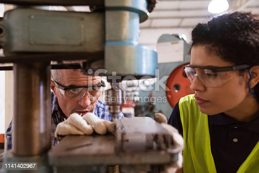 Instructor teaching female apprentice to use machinery. Engineer is with trainee in factory. They are in industry.
