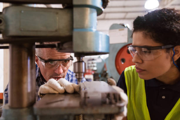 Engineer teaching female apprentice in factory Instructor teaching female apprentice to use machinery. Engineer is with trainee in factory. They are in industry. apprentice stock pictures, royalty-free photos & images