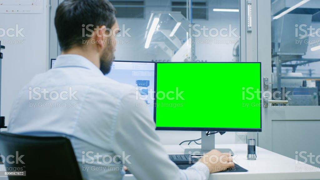 Ingenieur / Techniker arbeitet auf einem PC mit zwei Displays, man hat ein Green-Screen Chroma Key Vorlage großer für Mockup. Aus dem Büro Fenster Komponenten Manufacturing Factory gesehen. – Foto