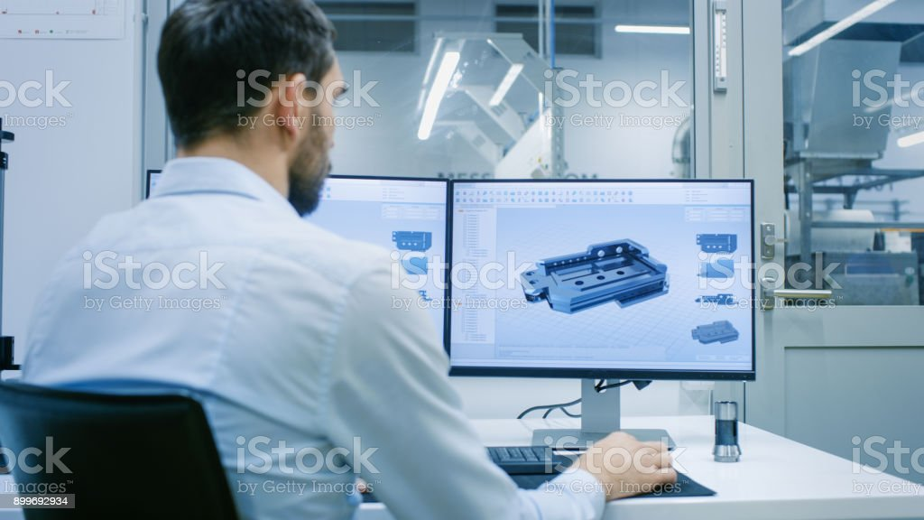 Engineer/ Technician Working on a Personal Computer with Two Displays, He's Designing New Component in CAD Program. Out of the Office Window Components Manufacturing Factory is Seen. stock photo