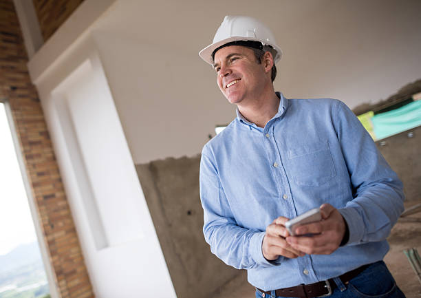 engineer texting at a construction site - civil engineer stock photos and pictures