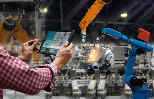 Engineer touch screen control robot the production of factory parts engine manufacturing industry robots and mechanical arm Engineer touch screen control robot the production of factory parts engine manufacturing industry robots and mechanical arm manufacturing stock pictures, royalty-free photos & images