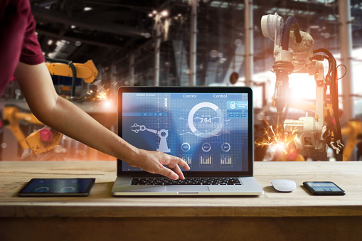 Engineer touching laptop to check and control welding robotics automatic arms machine in intelligent factory automotive industrial with monitoring system software. Digital manufacturing operation.Industry 4.0