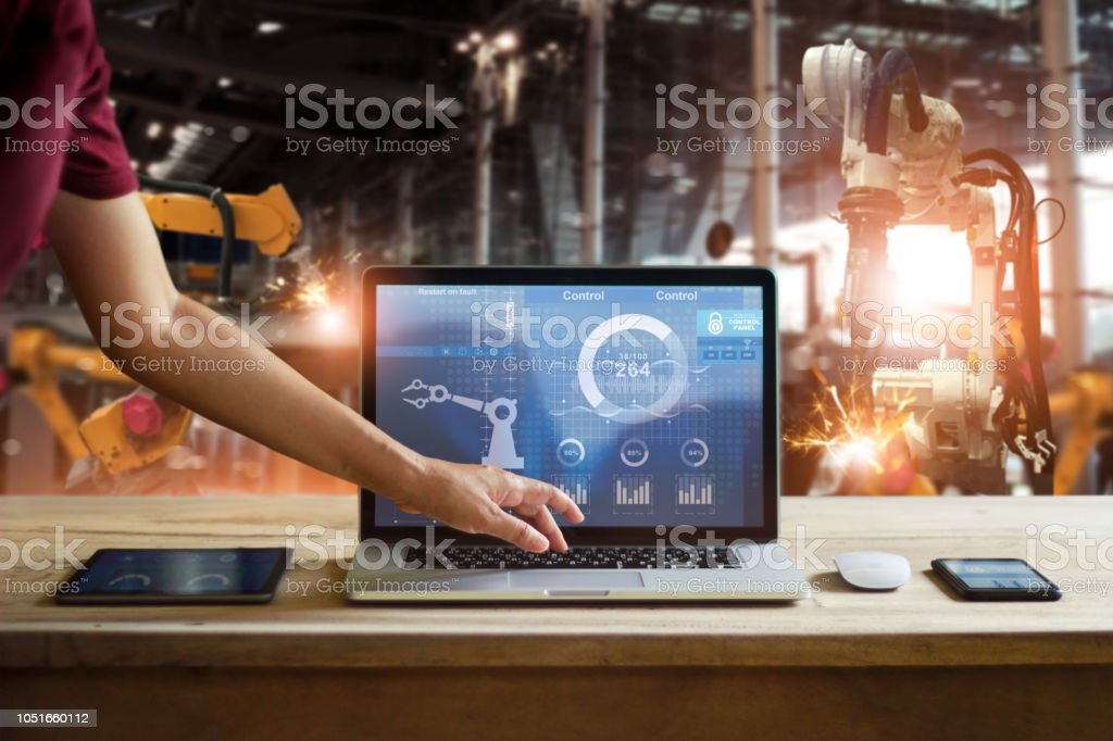 Engineer touching laptop check and control welding robotics automatic arms machine in intelligent factory automotive industrial with monitoring system software. Digital manufacturing operation.Industry 4. stock photo