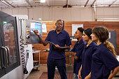istock Engineer Training Apprentices On CNC Machine 628110952