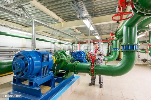 Engineer turns valve in industrial power generation station.