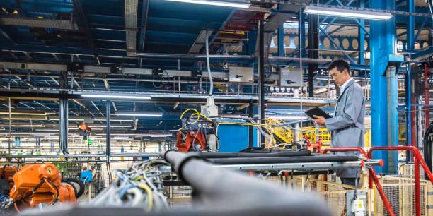 Ingenieur mit digitalem Tablet bei automatisierter Produktionsüberwachung – Foto