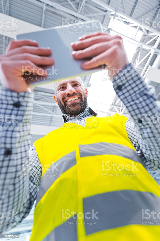 Engineer using a digital tablet, low angle view Engineer using a digital tablet in a industrial hall, smiling at camera, low angle view. Adult Stock Photo
