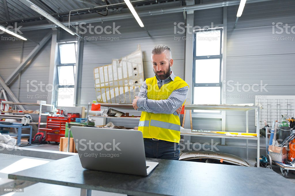 Engineer using a laptop at work Construction engineer using a computer at work.  Adult Stock Photo