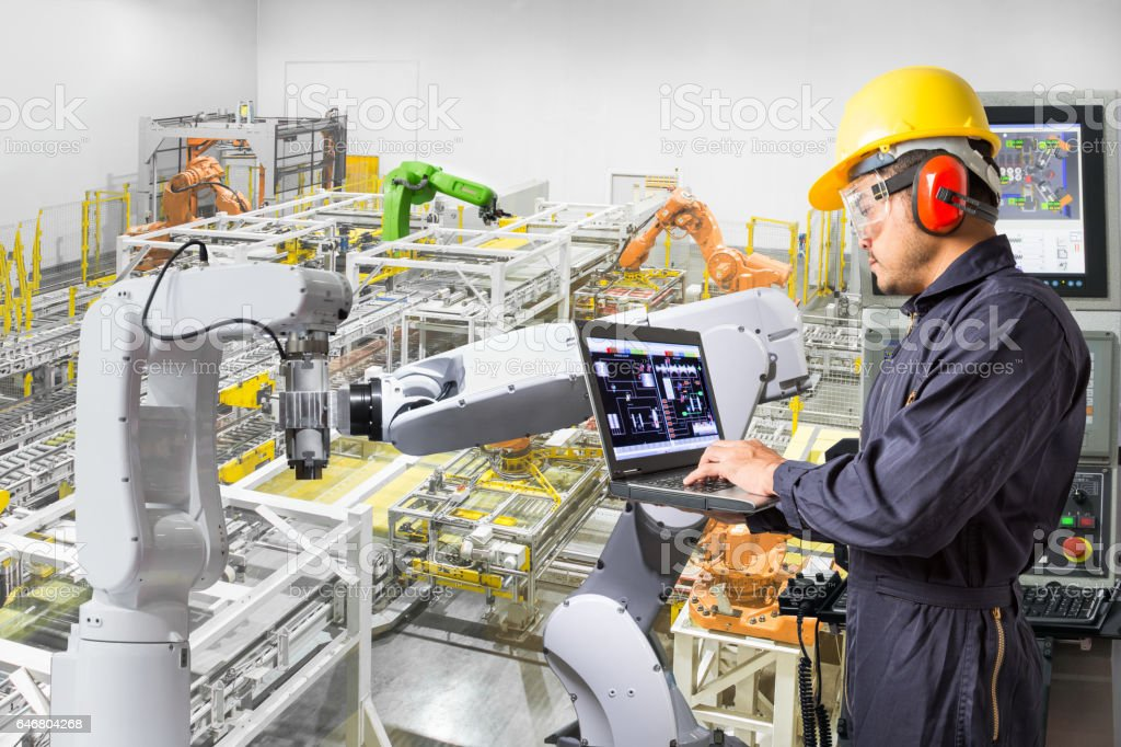 Engineer using computer for maintenance automatic robotic hand machine tool stock photo