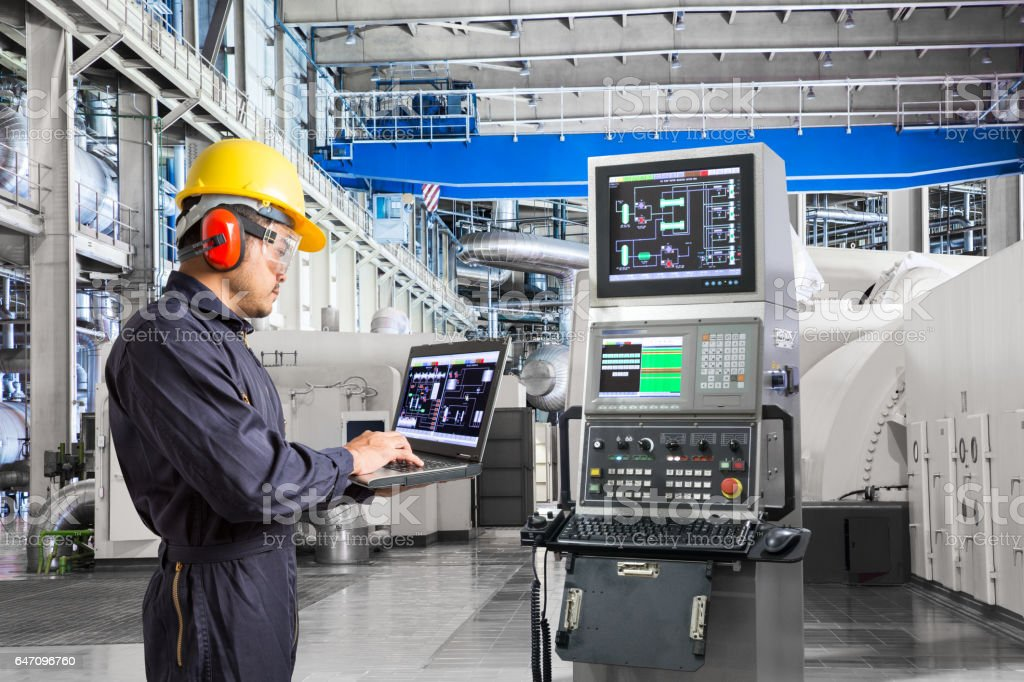 Engineer using computer for maintenance equipment in powerhouse stock photo