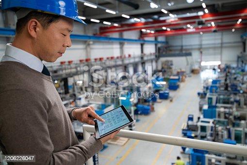 Engineer examining engineering drawing on digital tablet.