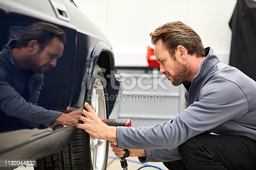 Side view of engineer using electric impact wrench on car wheel. Mid adult male technologist is repairing motorvehicle in industry. He is manufacturing retro style automobile in showroom.